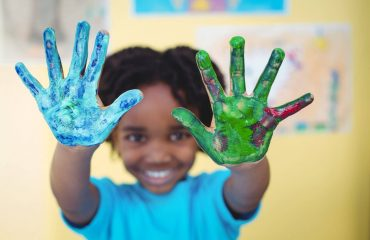 Smiling kid holding up his hands covered in paint